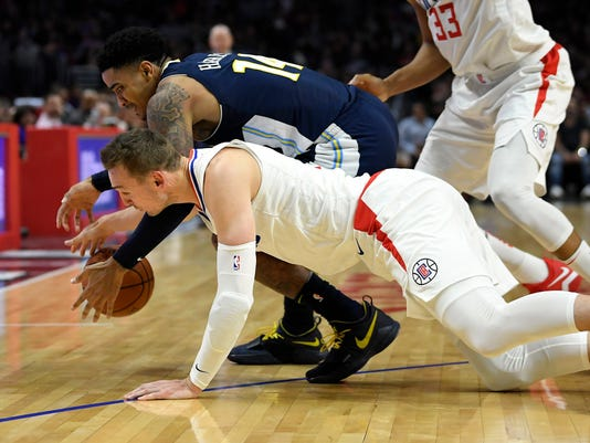Los Angeles Clippers forward Sam Dekker, below, and Denver Nuggets guard Gary Harris dive for a loose ball during the second half of an NBA basketball game, Wednesday, Jan. 17, 2018, in Los Angeles. The Clippers won 109-104. (AP Photo/Mark J. Terrill)