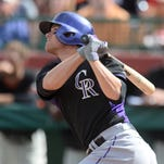 Mar 14, 2014; Scottsdale, AZ, USA; Colorado Rockies second baseman Josh Rutledge (14) follows through on a swing in the sixth inning at Scottsdale Stadium. Mandatory Credit: Joe Camporeale-USA TODAY Sports