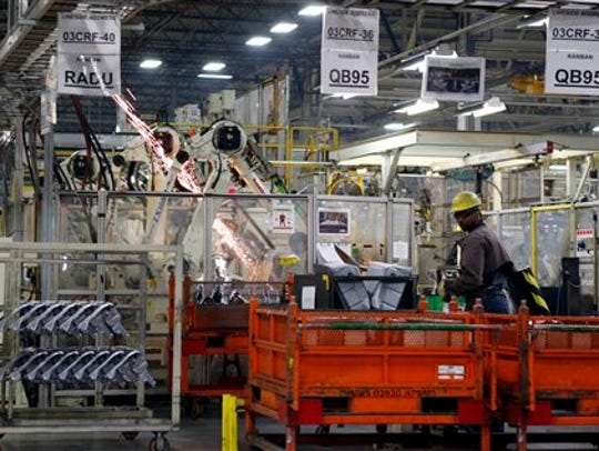 Sparks fly as robots weld on a Corolla assembly line,