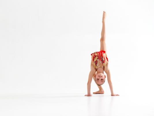 girl gymnast doing sports in rhythmic gymnastics on white background