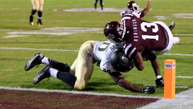 Mississippi State running back Josh Robinson (13) dives into the end zone and is hit by Vanderbilt defensive back Oren Burks (20) on Nov. 23, 2014.