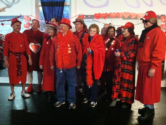 """A group enters the """"red dress"""" competition for the Red Dress Dash in Ankeny."""
