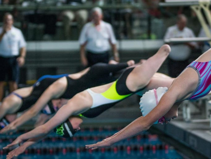 Swimmers dive off the blocks for the 100-meter freestyle.