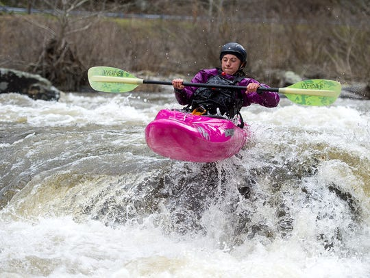 A kayaker takes flight as she rides a rapid March 25