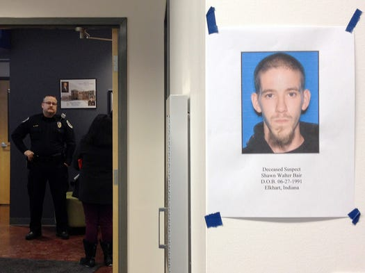 A photo of Shawn Walter Bair, right, hangs on a wall as Elkhart police wait for the start of a news conference Thursday, Jan. 16, 2014, in Elkhart, Ind. Authorities identified Blair as the man who fatally shot two women in a northern Indiana grocery on Wednesday.