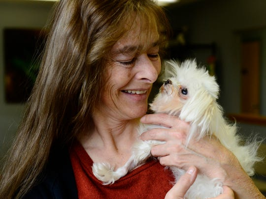 Cheryl Garcia holds Elliott the dog. The pet died Dec. 5 due to complications of oral surgery.