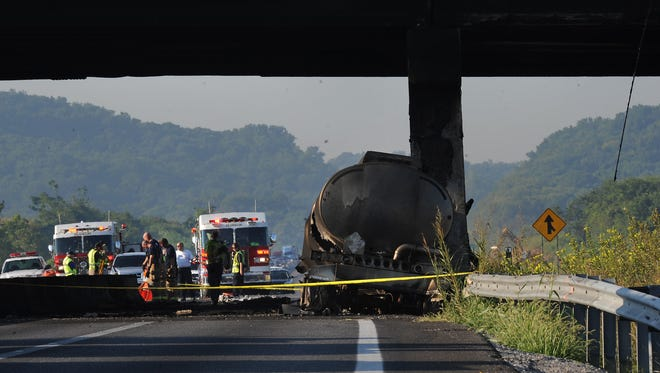 Officials look over the remains of the tanker truck that crashed and exploded Friday Aug. 15, 2014 on Interstate 65 in Franklin.