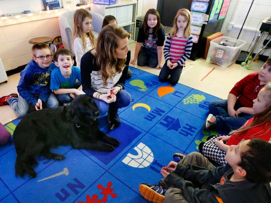 Students gather around Paige Saylors and her service dog, Inca, during a classroom lesson at Christiana Elementary.