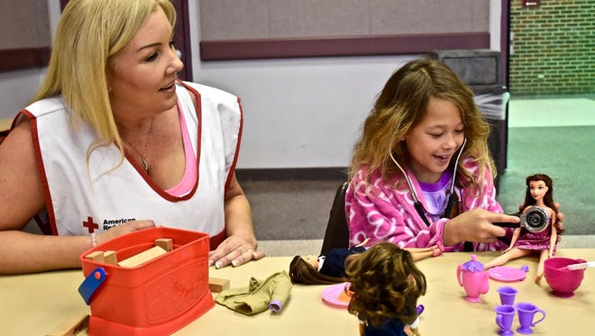 Eight-year old Jersie Reyes, a resident in a Bossier City, Red Cross shelter, was hosting a tea party with her dolls when American Red Cross nurse Stacie Archibald asked her if she would like to listen to her doll's heart. She was disappointed when she heard nothing from her doll, but her face lit up when Stacie put the stethoscope over her own heart. Then, Jersie was fascinated to listen to the beat of her own heart.