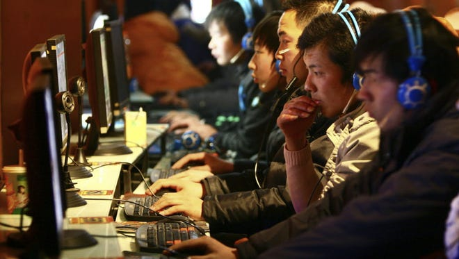 In this file photo taken Friday, Jan. 15, 2010, people use computers at an Internet cafe in Fuyang in central China's Anhui province. As cyber security professionals gather in San Francisco this week, it's likely some firms will release news of breaches and vulnerabilities.