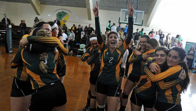 Catholic's volleyball team celebrates after winning the Region 1-4A title game against Fernandina Beach Saturday at Catholic High School.