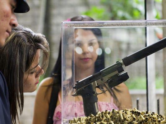 Visitors look at a 9mm Sig Sauer P226 ta