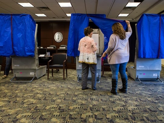 Volunteer Kiley Edwards helps a voter into a booth at the Middletown Town Council Chambers on Monday afternoon. Three incumbents were re-elected.