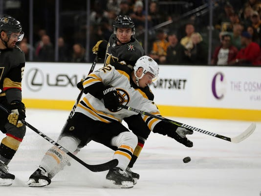 Boston Bruins center Frank Vatrano (72) knocks down a loose puck as Vegas Golden Knights defenders close in during an NHL hockey game at T-Mobile Arena, Sunday, Oct. 15, 2017, in Las Vegas. (AP Photo/L.E. Baskow)