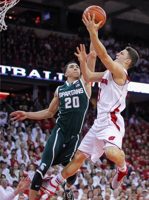 Wisconsin's Zak Showalter, right, shoots against Michigan State's Travis Trice during the second half Sunday in Madison.