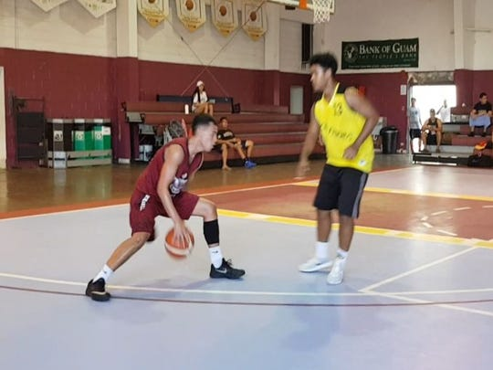 Tamuning Typhoons Billy Belger works around Microfriends Bret Kusto in Men's Varsity action during GTA Holiday TipOFF action at the Tamuning Gym.