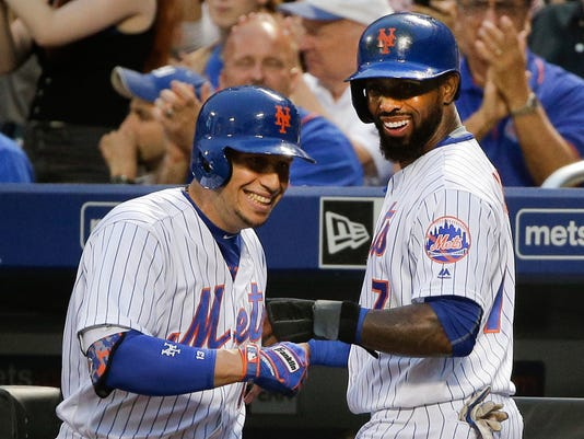 New York Mets' Jose Reyes, right, is greeted by Asdrubal Cabrera after scoring on a sacrifice fly by Neil Walker during the first inning of a baseball game against the Washington Nationals, Saturday, July 9, 2016, in New York. (AP Photo/Julie Jacobson)