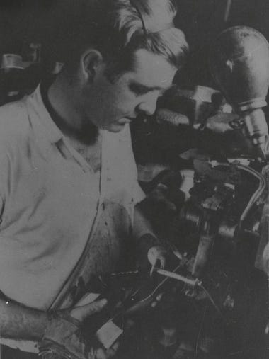 An Endicott Johnson worker completes a shoe, about