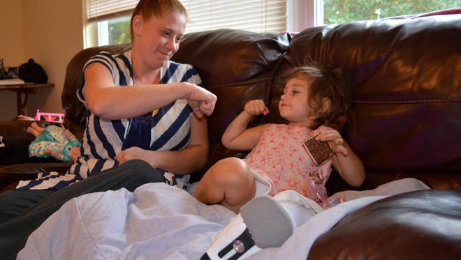 Two-year-old Victoria Lynn Jenkins gets a fist bump from her mother, Heather, in their Ocean View home. Victoria Lynn is recovering after being shot in the leg Aug. 30.