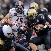 Army quarterback Angel Santiago, right, rushes the ball against Navy linebacker Jordan Drake (13) in December during the first half of a college football game in Baltimore. With Navy joining the American Athletic Conference, the Midshipmen are eligible to earn a bid to a New Year's Six bowl.