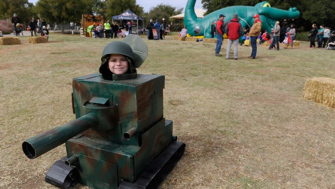 Wyatt Stevens, 12, kneels while wearing his homemade tank costume at Boo at the Zoo on Saturday at the Abilene Zoo. This is the second version of this costume, Wyatt said. He was inspired by a video game but it didn't work for him. His father, Dare, helped him with this version, though they incorporated parts of the first in the new design.