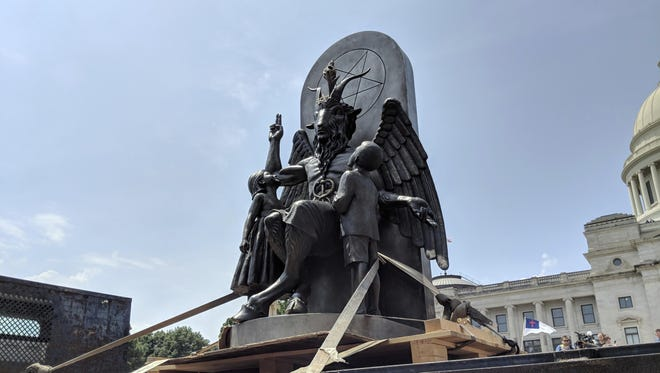 The Satanic Temple unveils its statue of Baphomet, a winged-goat creature, at a rally for the first amendment in Little Rock, Ark., Thursday, Aug. 16, 2018.