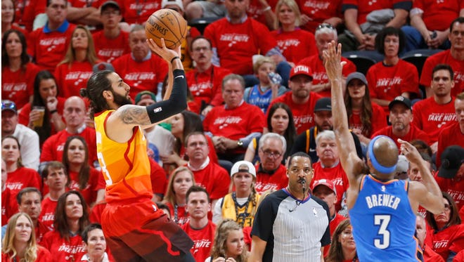 Utah Jazz guard Ricky Rubio, left, shoots as Oklahoma City Thunder forward Corey Brewer, right, defends in the first half during Game 3 of an NBA basketball first-round playoff series Saturday, April 21, 2018, in Salt Lake City.
