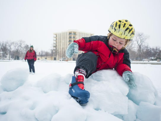 Finnegan Frisbie, 4, climbs a pile of ice and snow
