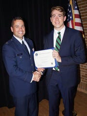 Davis Schiller (right) accepts his Certificate of Appointment document from retired Air Force Admissions Officer Lt. Col. Joseph Troy Morgan. Schiller was nominated for the service academy by Michigan's U.S. Senator Gary Peters.