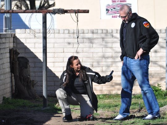 A Carlsbad Police Department evidence technician recovers a handgun tossed by a suspect into a neighboring  yard.