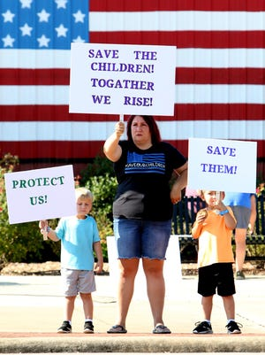 Kooper Fanick, 4, left, Shawna Schulp and Braxton Fanick, 5, stand at the corner of Second and Broadway, Saturday, Aug. 22, 2020, holding posters calling attention to the nationwide Save Our Children rally.