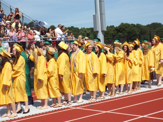 Franklin D. Roosevelt graduates form a procession line Saturday as they enter the school's new outdoor athletic complex.