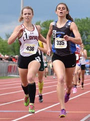 McConnellsburg's McKenzie Gelvin (right) crosses the finish line in a girls 2A 800 prelim at the 2017 PIAA track & field championships held at Shippensburg