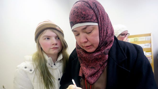 Angela Lewis, right, with her daughter, Sophie, leaves a note for U.S. Rep. Mike Gallagher Wednesday, Feb. 2, 2017, in Appleton, Wis. Protesters gathered near Houdini Plaza to voice their opposition to policies put forth by President Donald Trump during the Peaceful Protest for a United America rally.