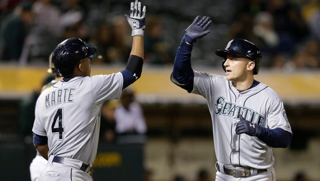 Seattle Mariners' Kyle Seager, right, celebrates with Ketel Marte (4) after hitting a two-run home run off Oakland Athletics' Drew Pomeranz in the ninth inning of a baseball game Friday, Sept. 4, 2015, in Oakland, Calif.