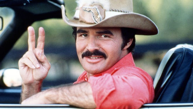 """Burt Reynolds, seen here in his box office hit """"Smoky & The Bandit,"""" has died at 82."""