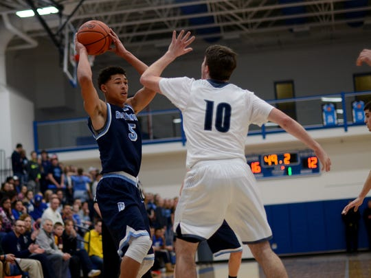 Richmond Blue Devils' D'Sean Hamilton tries to find an open teammate Monday, Mar. 7, during district basketball against Yale at Croswell-Lexington High School..