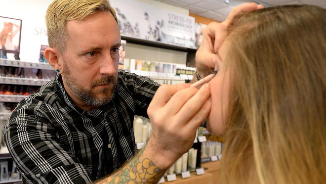 Christopher Endsley, a colorist at Douglas J Salon and Day Spa, applies eyeliner on Karleigh Madaj.