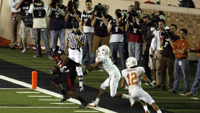 Texas Tech wide receiver Michael Crabtree moves out of the hold of Texas' Curtis Brown and teammate Earl Thomas to score the game-winning touchdown to help the No. 6 Red Raiders defeat No. 1 Texas on Nov. 1, 2008 in Lubbock.