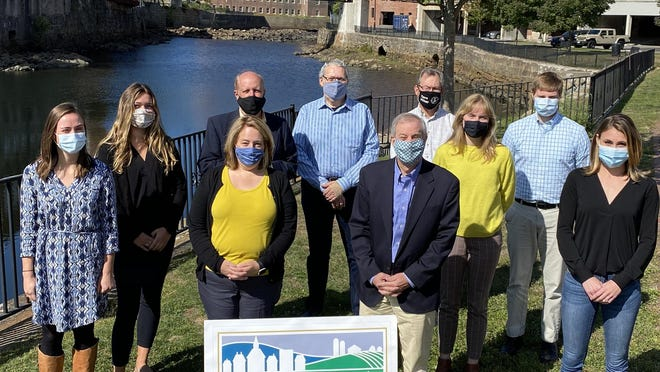 The staff of Southern Maine Planning and Development Commission gather outside their offices along the Saco River in Saco, Maine.