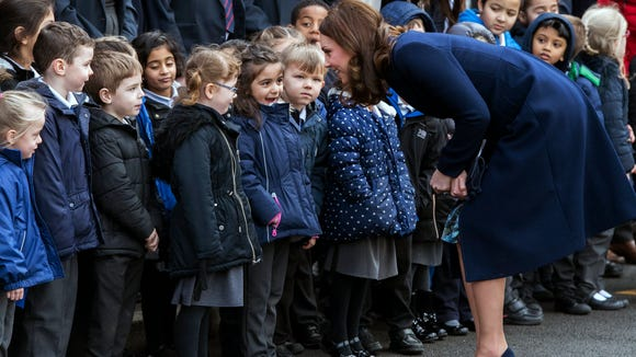 Kate, clad in a navy overcoat and matching suede heels,