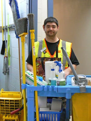 Garten Services custodial employee Marshall Brown shows off his cleaning cart loaded with Green Seal certified cleaner.