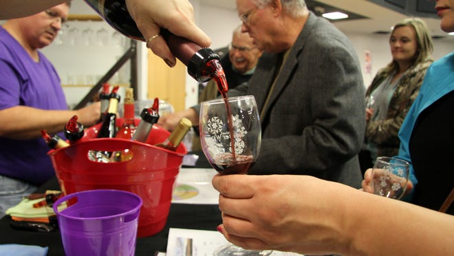 Virginia Snyder of Shattuck Vineyard pours a glass  of red wine at the Carlsbad Winter Wine Festival on Saturday.
