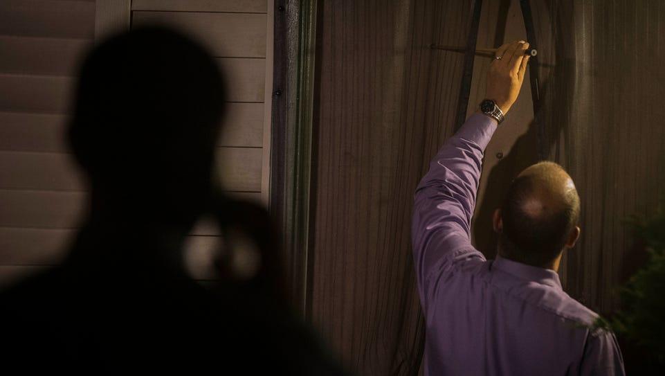 Burlington police investigators measure a bullet hole