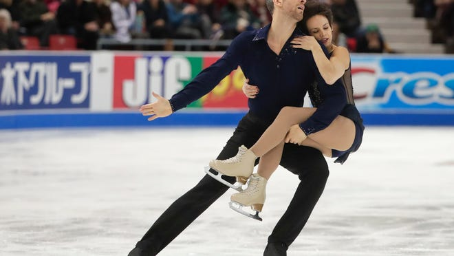 FILE - In this Nov. 24, 2017, file photo, Meagan Duhamel, right, and Eric Radford, left, of Canada, perform during the pairs short program at the Bridgestone Skate America in Lake Placid, N.Y. Duhamel and Radford are focused squarely on the Pyeongchang Olympics, where the pairs team from Canada will contend for a gold medal inside Gangneung Ice Arena in the next couple weeks. (AP Photo/Julie Jacobson, File)