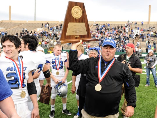 Richland Springs head football coach Jerry Burkhart holds the state championship trophy after his Coyotes defeated Follett 60-14 for their sixth state title in 2012.