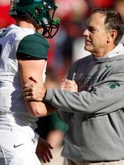 Coach Mark Dantonio talks to quarterback Connor Cook (18) before MSU's win at Nebraska on Nov. 11, 2013.