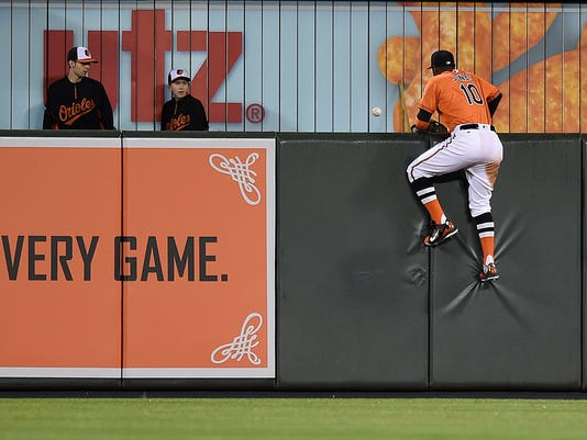 Baltimore Orioles center fielder Adam Jones climbs the wall reaching for a two-run home run hit by Chicago White Sox's Todd Frazier during the eighth inning of a baseball game, Saturday, April 30, 2016, in Baltimore. The White Sox won 8-7. (AP Photo/Gail Burton)