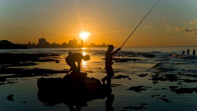 In this 2016 photo, fishermen throw their fishing rods.