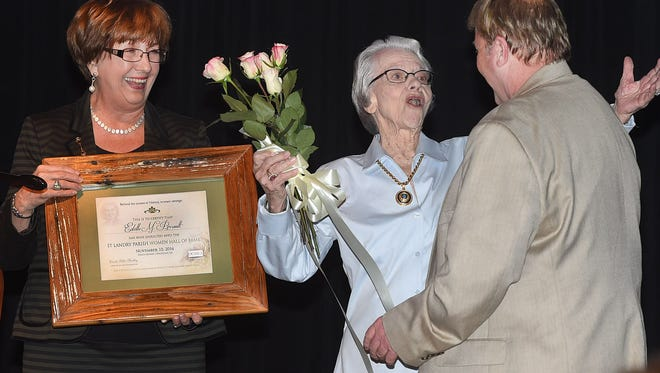 Estelle Perrault, shown here receiving a framed certificate and bouquet of flowers, was one of the five St. Landry Parish Women Hall of Fame inductees in 2016.  The event was presented by the OGMLA Foundation.